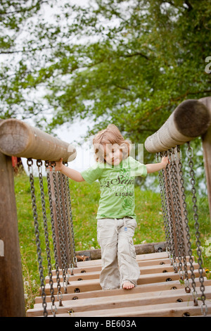 Boy, 3 years old, running across a chain bridge at a playground - Stock Photo