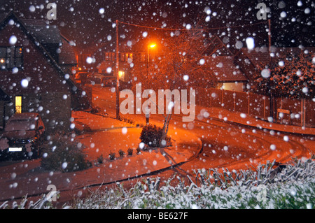 Snow flakes by flash with orange lighting illuminating snow covered residential street landscape - Stock Photo