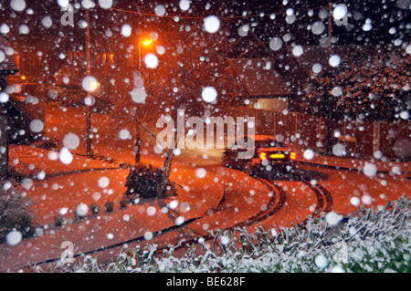 Snow flakes by flash with orange lighting illuminating snow covered residential street landscape car driving along - Stock Photo