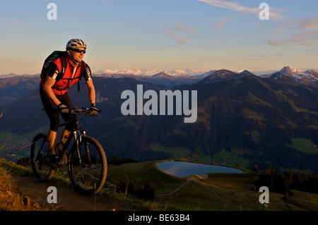 Mountainbiker at Hohe Salve mountain in the evening light, Tyrol, Austria, Europe - Stock Photo