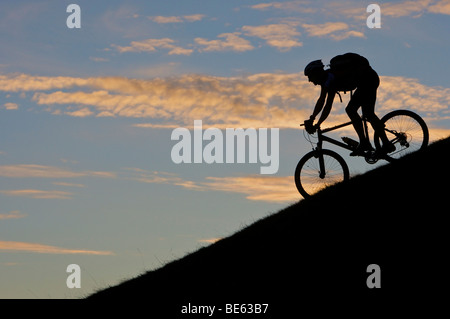 Mountainbiker, silhouette at Hohe Salve mountain in the evening light, Tyrol, Austria, Europe - Stock Photo