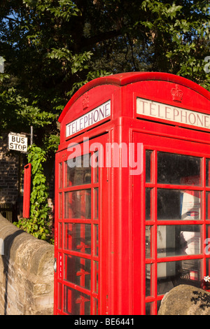 UK, England, Yorkshire, Haworth, old red K6 Phone box and bus stop outside railway station - Stock Photo