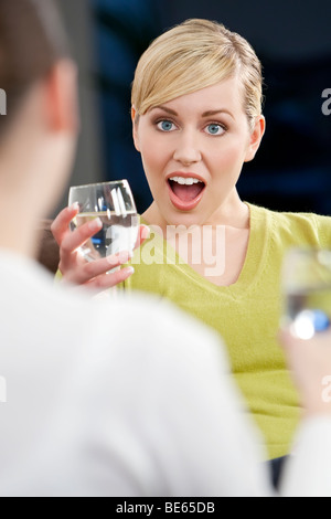 A beautiful young blond woman with a surprised look on her face while chatting with a friend over a drink - Stock Photo