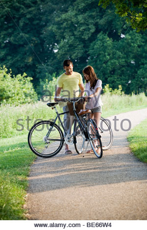 A young couple standing with bicycles holding a map - Stock Photo