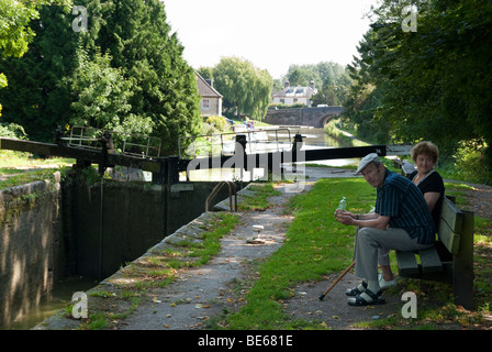 elderly couple on bench by lock gates on Kennet and Avon Canal - Stock Photo