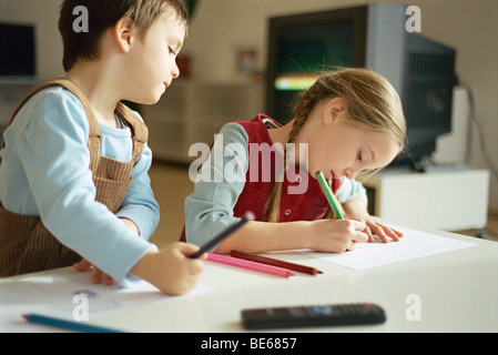 Siblings drawing with colored pencils, little boy pausing to look over sister's shoulder - Stock Photo