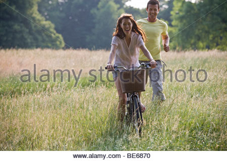 A young woman riding a bicycle through a field with her boyfriend running after her - Stock Photo