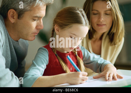 Little girl drawing, parents sitting on either side, watching over her shoulder - Stock Photo