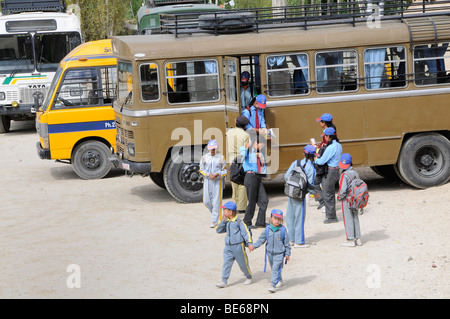 Elementary school students in school uniform coming from a school bus of the Indian army, Secondary Senior School, - Stock Photo