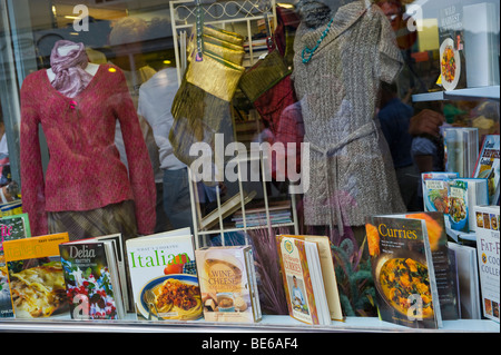 Display of cookery books and clothes for sale in charity shop during Abergavenny Food Festival Monmouthshire South - Stock Photo