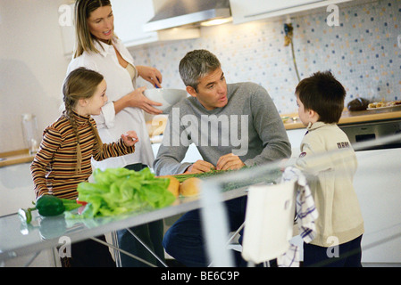 Family together in kitchen all listening to little boy - Stock Photo