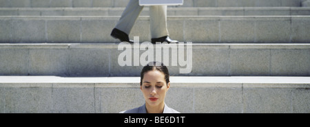 Woman on steps with eyes shut, businessman walking in background - Stock Photo