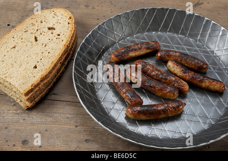 Nuernberger bratwurst in an iron pan with bread - Stock Photo