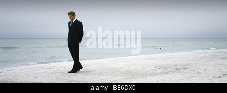 Man in suit walking on beach - Stock Photo