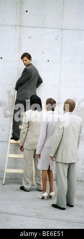 Businessman climbing ladder, looking over shoulder at professionals lined up behind him - Stock Photo