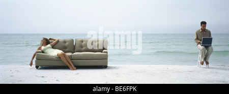 Woman reclining on sofa on beach, man on stool using laptop computer nearby - Stock Photo