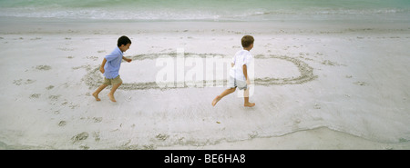 Boys running on beach, chasing each other around circle drawn in sand - Stock Photo