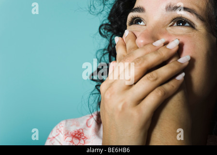 Woman covering mouth with hands, portrait - Stock Photo