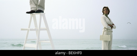 Woman on beach with folded arms watching man standing on top of ladder, cropped - Stock Photo