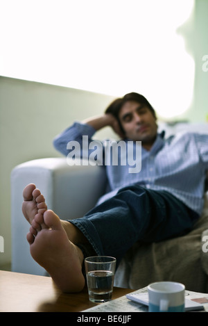 Man sitting on sofa with feet up on coffee table - Stock Photo