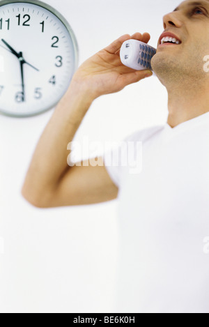 Man on phone call, clock in background - Stock Photo