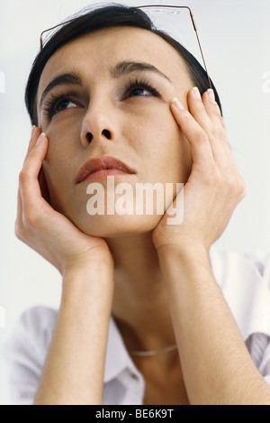 Woman holding head, looking up - Stock Photo