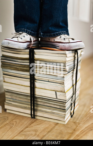 Person standing on top of bound stack of books and magazines - Stock Photo