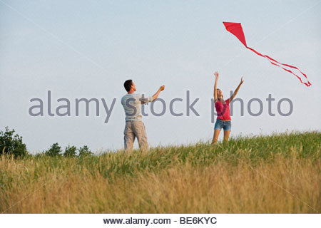 A young couple flying a red kite - Stock Photo