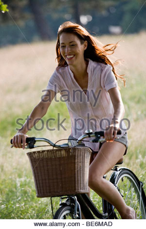 A young woman riding a bicycle in summertime - Stock Photo