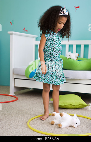 Little girl playing with plastic hoop and stuffed toy in bedroom - Stock Photo