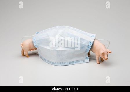 Swine flu concept, flu mask and toy pigs - Stock Photo