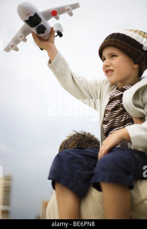 Little boy sitting on father's shoulders, holding up toy airplane - Stock Photo