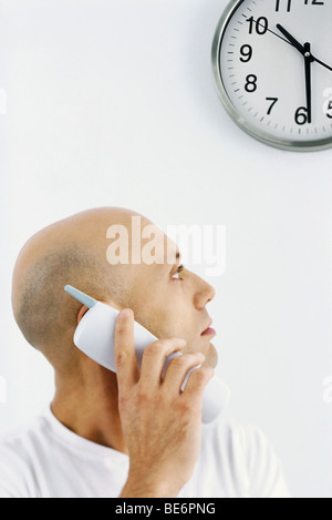 Man on phone call, looking over shoulder at clock - Stock Photo