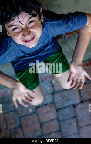 Young boy sits on front porch steps in the rain holding hands open to sky - Stock Photo