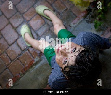 Young boy sits on front porch steps in the rain looking behind him upwards with a smile on his face - Stock Photo