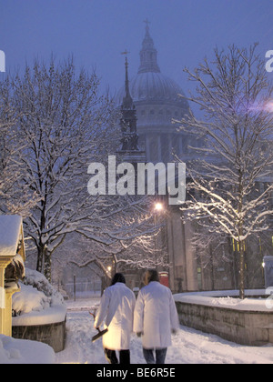 People walk through snow near St Paul's Cathedral in central London - Stock Photo