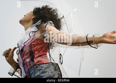 Side View Of Woman Wearing Raincoat Drenched In Water