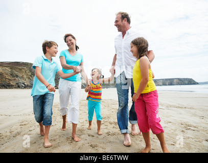 Woman, man, two girls and a boy walking along the beach, hand in hand, laughing - Stock Photo