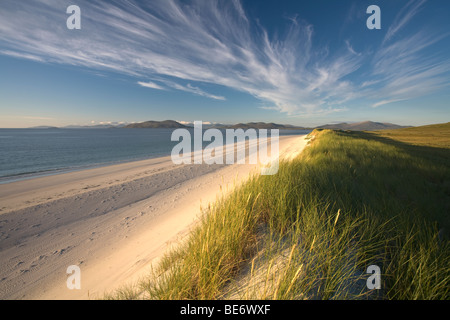 Strong summer sun lights the beach and dunes under dramatic streamers of cloud on Berneray in the Western Isles - Stock Photo