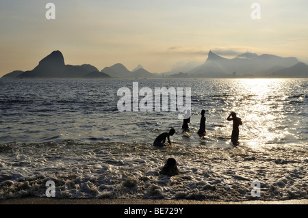 Young people in the ocean and view of the Sugarloaf Mountain and Corcovado Mountain, Niteroi, Rio de Janeiro, Brazil, - Stock Photo