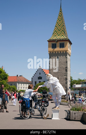 Lindau, Bavaria, Germany. Living statue mime artist greeting tourist on waterfront promenade in picturesque Old - Stock Photo