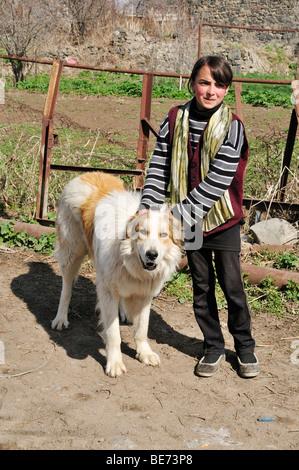 Armenian girl with a shepherd dog in a poor mountain village near Sisian, Armenia, Asia