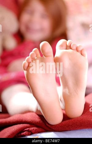 Little girl lying on a sofa cushion and laughing, barefoot - Stock Photo