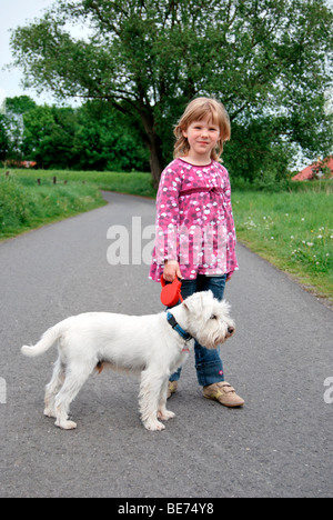 Girl, 5, standing on a path with a white Miniature Schnauzer - Stock Photo