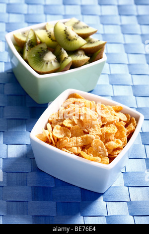 Cornflakes and kiwi slices in bowls - Stock Photo