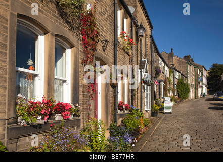 UK, England, Yorkshire, Haworth, Main Street, houses with floral planting outside - Stock Photo