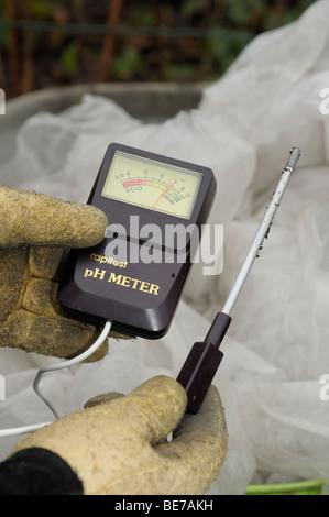 holding a soil ph meter. - Stock Photo