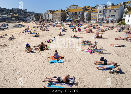 Sunbathers on a sandy beach in St Ives harbour - Stock Photo