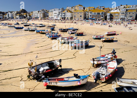 Fishing boats beached on the sand in a harbour at low tide - Stock Photo