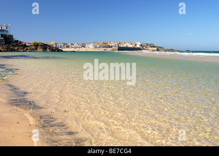 A clear sea laps a sandy beach with St Ives in the background - Stock Photo